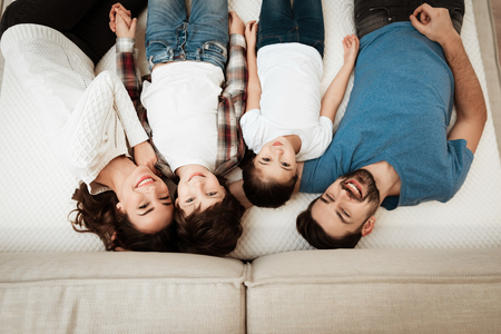 Happy family enjoys comfort of lying on a mattress inside a furniture store. Big family together check softness of mattress.