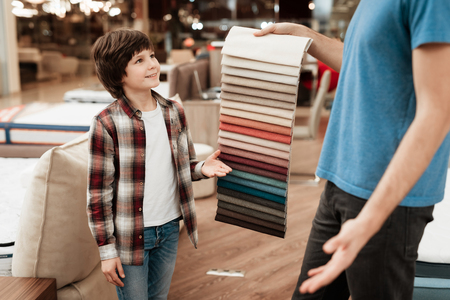 Man with young boy chooses color on color palette. Selecting color of mattress on color palette guide. Selection of color of cloth in color catalog. Stock Photo