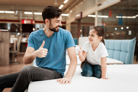 Bearded handsome man with daughter sitting on mattress. Choosing mattress in store. Happy family in store of orthopedic furniture. Imagens