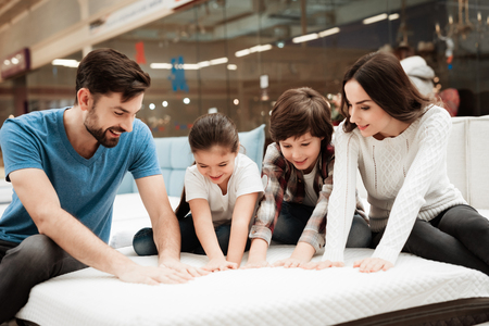 Big happy family testing orthopedic mattress in shop of furniture. Check softness of mattress. Happy family in store of orthopedic furniture. Archivio Fotografico
