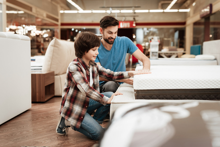 Bearded man with young son is testing mattress for softness. Testing softness of mattress. Choosing mattress in store