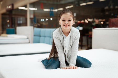 Happy little girl sitting on mattress in mattress store. Choosing mattress in store. Check the softness of the mattress.