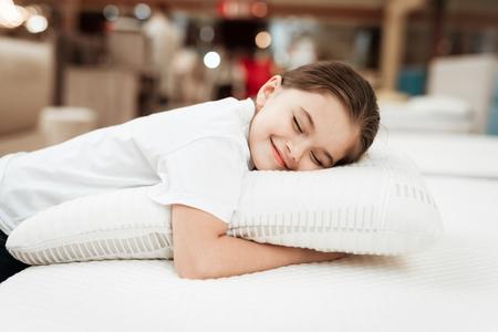 Nice little girl hugs pillow in store of orthopedic mattresses. Testing softness of pillow. Check softness of orthopedic pillow. 写真素材