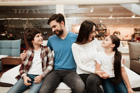 Happy family sitting on soft mattress in orthopedic furniture store. Healthy posture concept. Testing softness of mattress. Choosing mattress in store