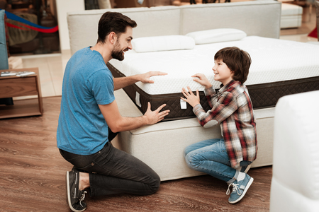 Confident bearded father with small boy choose orthopedic mattress in furniture store. Choosing mattress in store. Healthy posture concept