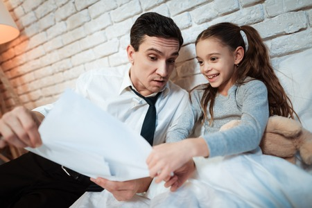 Young father tells his daughter about his work. Businessman shows little daughter than he does. Father shows his daughter what he is working on. Archivio Fotografico