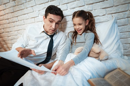 Young father tells his daughter about his work. Businessman shows little daughter than he does. Father shows his daughter what he is working on. Reklamní fotografie