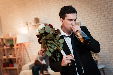 Adult man with a bouquet drinks whiskey. Male alcoholic trouble in family. Young family is upset that father was drunk. Stock Photo - 97645841