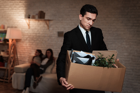 Businessman leaves house with stuff box. Father leaves home because of problems in family. Family problems. Businessman is carrying box. Stok Fotoğraf