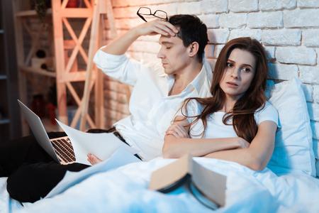 ベッドに座ってラップトップで働く疲れたビジネスマン。若者は仕事にうんざりしている。若い女の子は、男が絶えず働いていることに失望してい