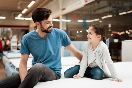 Bearded handsome man with daughter sitting on mattress. Choosing mattress in store. Happy family in store of orthopedic furniture. Archivio Fotografico - 97680016