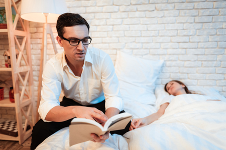 Young businessman sits on bed next to young woman and reads book. Woman is asleep. Woman fell asleep, because she was overtired.