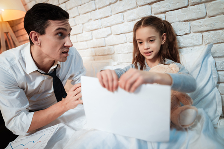 Little girl does not let her father work. Little daughter is tearing up her fathers papers. Daughter requires attention of busy father. Stock fotó