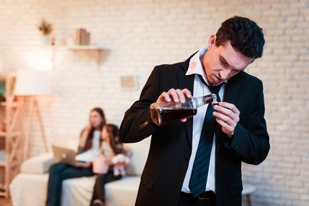 Drunk man in suit drinks alcohol at home. Family alcoholic. Drinking alcohol. Adult man abuses alcohol. Man is holding bottle of whiskey. Stock Photo - 97680020