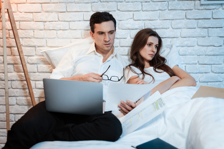 Young businessman sitting in bed working on laptop. Man is studying documents. Young girl is disappointed that man is constantly working.