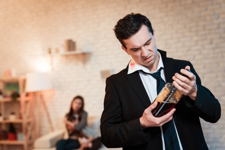 Drunk man in suit drinks alcohol at home. Family alcoholic. Drinking alcohol. Adult man abuses alcohol. Man is holding bottle of whiskey. Stock Photo - 97680024