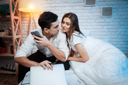 Young woman distracts from the work businessman from working on laptop. Young girl sticks to man in white shirt. Man is holding cell phone.