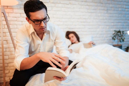 Young businessman read book near sleeping young woman. Man in glasses concentrated on reading book. Handsome man enthusiastically reading book. Beautiful woman is sleeping near young man.