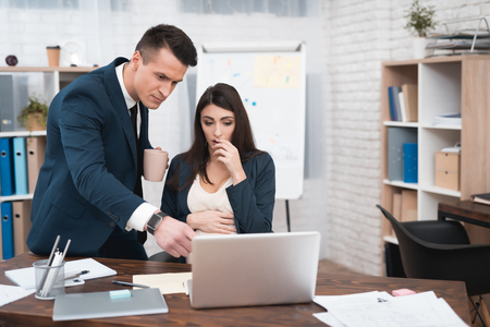 Young disgruntled man in suit scolds pregnant girl for mistakes in work done. Pregnant girl has problems at work. Young man in suit scolds young pregnant woman. Banco de Imagens - 97680204