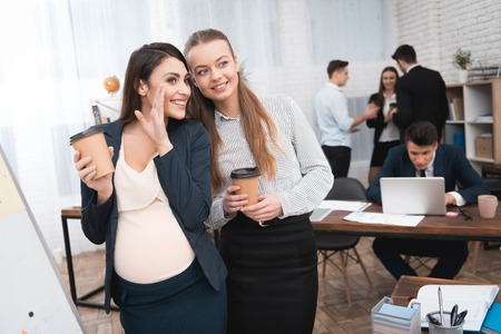 Two young girls spread gossip on coffee break. Gossip in the office. Pregnant girl with her pretty girlfriend is drinking coffee. Stock Photo