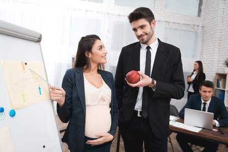 Bearded young man in suit offers pregnant woman snack with apple. Pregnant girl in office. Pregnant girl with young bearded man is studying charts.