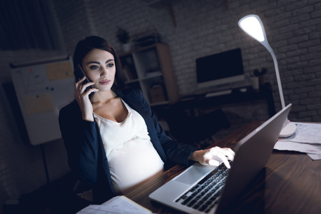 Beautiful pregnant girl working on laptop. Pregnant in dark office. Pretty pregnant woman is working on laptop in dark office. Stock Photo