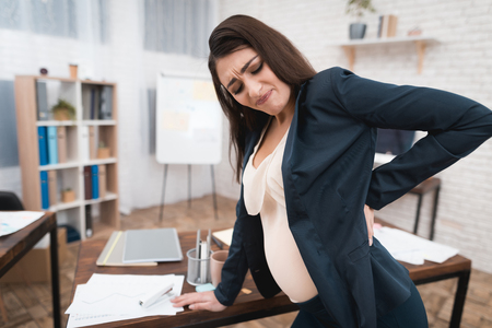 Pretty pregnant girl is experiencing labor in office. Pregnant in office. Pregnant belly. Pregnancy. Pregnant in office.