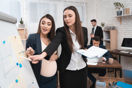 Young girl with pregnant woman disassembles workflows on flipchart. Pregnancy in the office. Pregnant woman works with girl colleague in front of flipchart. Stock Photo