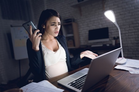 Beautiful pregnant girl is upset because of phone call. Upset pregnant girl in office alone. Pregnant in office. Unhappy pregnant girl works behind laptop.