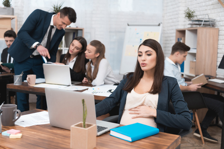 Young pregnant girl is working in office with colleagues. Pregnant businesswoman in office. Teambuilding. Pregnant woman works behind laptop. Stock Photo