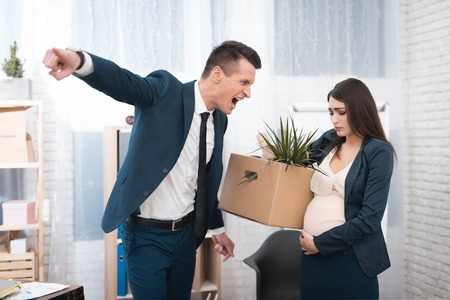 Young angry chief screams and fired upset pregnant girl with stuff box in office. Pregnant young woman is fired from job. Pregnant woman left work.