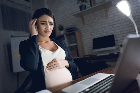 Young pregnant woman work at home alone. Pregnant woman experiences a headache. Young pregnant woman holding pregnant belly.