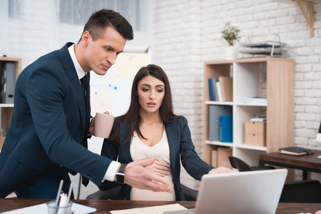 Young disgruntled man in suit scolds pregnant girl for mistakes in work done. Pregnant girl has problems at work. Young man in suit scolds young pregnant woman.
