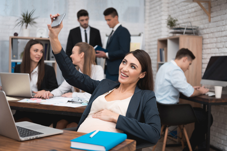 Pregnant woman doing selfie on phone in office. Pregnant woman with working team. Beautiful pregnant girl is holding her pregnant belly. Stock Photo