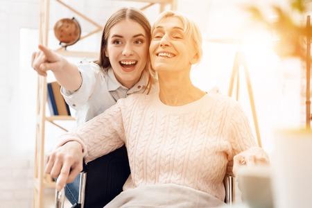 La ragazza si prende cura della donna anziana a casa. La ragazza sta guidando la donna in sedia a rotelle. Loro sono felici. Archivio Fotografico - 97680523