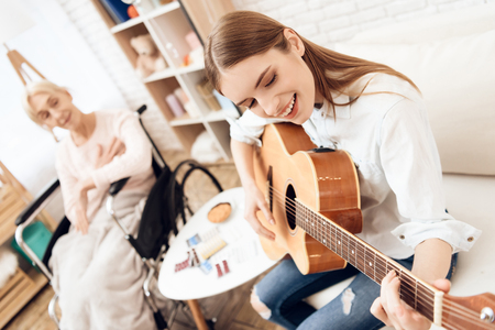 Girl is nursing elderly woman in wheelchair at home. Girl is playing on guitar for woman.