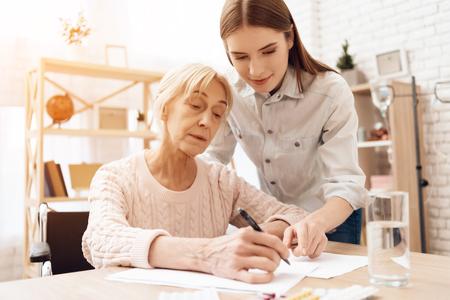 La muchacha está amamantando a una anciana en silla de ruedas en casa. La muchacha está ayudando a la mujer a escribir.