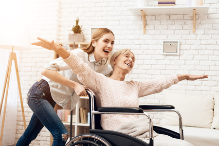 Girl is nursing elderly woman at home. Girl is riding woman in wheelchair. Woman feels like flying. They are happy. Banco de Imagens