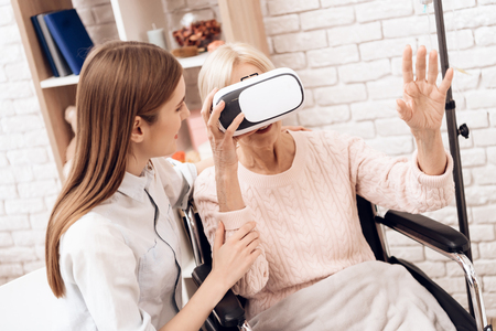 Girl is caring for elderly woman in wheelchair at home. Woman is using virtual reality.