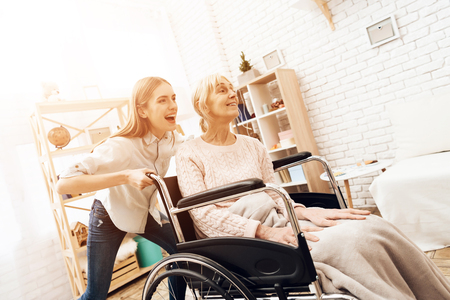 Girl is nursing elderly woman at home. Girl is riding woman in wheelchair. They are happy.