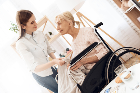 Girl is nursing elderly woman in wheelchair at home. Girl is covering woman with warm blanket.