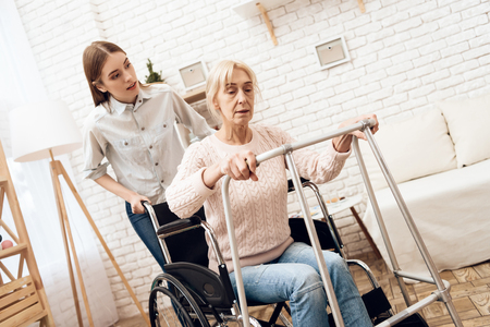 Girl is nursing elderly woman at home. Woman is trying to stand up from wheelchair with help of walker.
