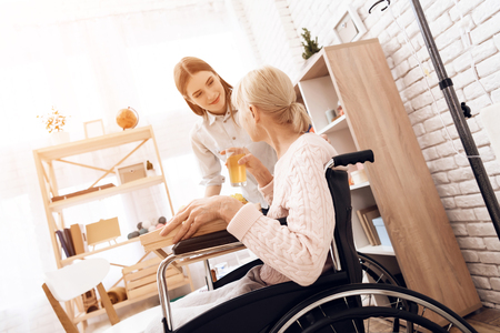 Girl is caring for elderly woman in wheelchair at home. Girl brings breakfast on tray. Woman is drinking juice. Standard-Bild