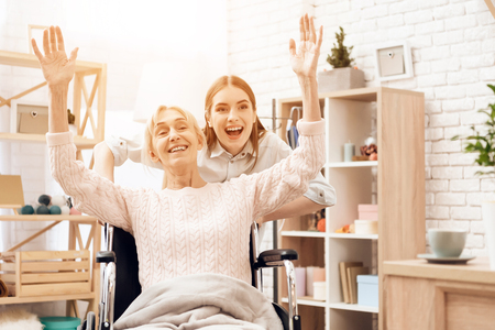 Girl is nursing elderly woman at home. Girl is riding woman in wheelchair in living room. They are happy. Banco de Imagens
