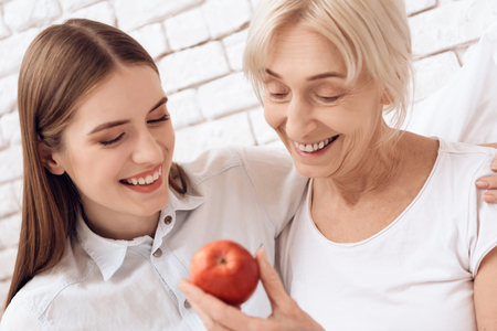 Girl is nursing elderly woman in bed at home. They are embracing. Woman is holding apple. Stock Photo
