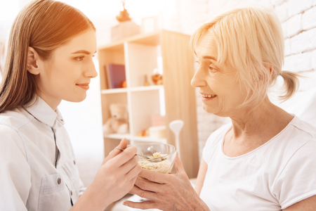 Girl is nursing elderly woman in bed at home. Girl is helping woman with food. Stock Photo