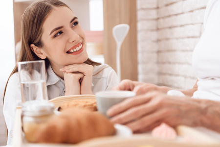 Girl is caring for elderly woman in bed at home. Girl brings breakfast on tray. Girl is smiling.
