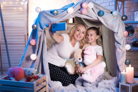 Grandmother and granddaughter are taking selfie in cozy blanket house at night at home.