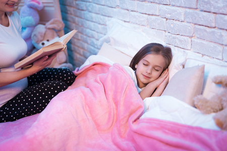 Grandmother reading book while granddaughter is lying in bed at night at home. Imagens