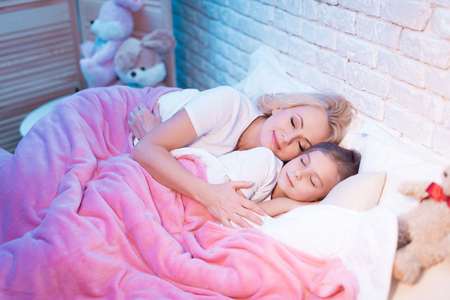 Grandmother and granddaughter are lying in bed ready for sleep at night at home.